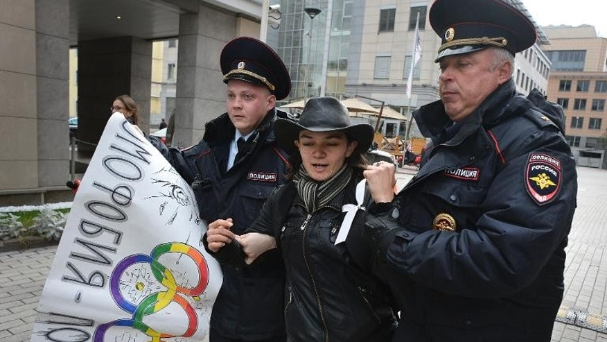 Police detain a gay rights activist during an unauthorized protest against Russian laws banning the promotion or display of homosexuality outside the headquarters of the Sochi 2014 Organizing Committee in Moscow on September 25, 2013.