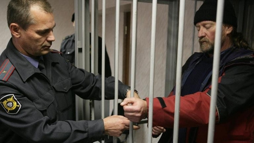 A handout picture taken late on September 26, 2013, and provided by Greenpeace International shows Greenpeace International activist from Canada Paul Ruzycki standing in a defendant cage in a court in the northern Russian city of Murmansk.