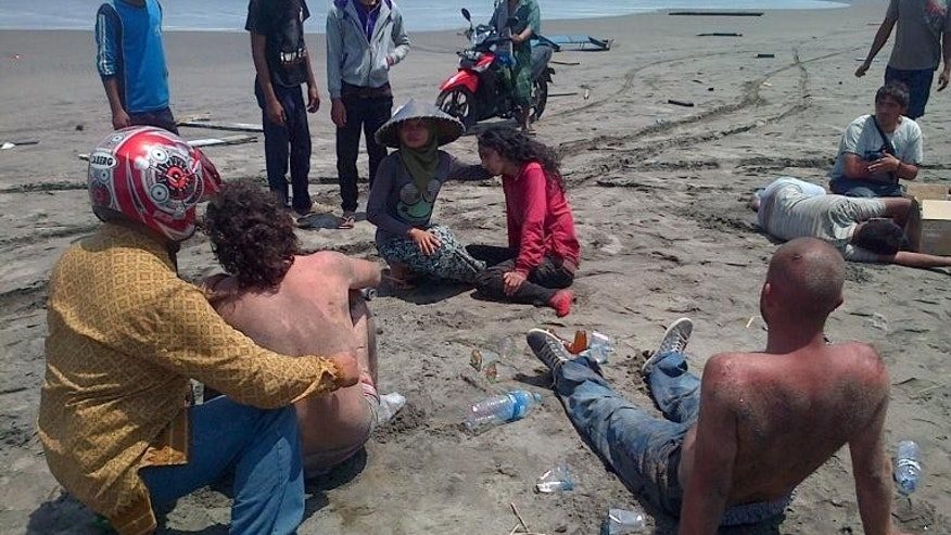 Residents help a group of asylum-seeker survivors on the beach after being rescued by locals in the coastal village of Cianjur located in Indonesia's western Java island on September 27, 2013