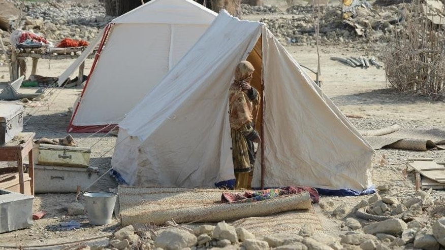 A Pakistani earthquake survivor stands outside her tent near collapsed mud houses in the Dhall Bedi Peerander area of the earthquake-devastated district of Awaran on September 27, 2013