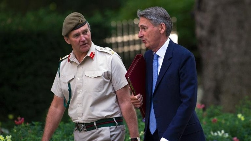 British Defence Secretary Philip Hammond (R) walks with Britain's Chief of the Defence Staff, General Nick Houghton, in London on August 28, 2013