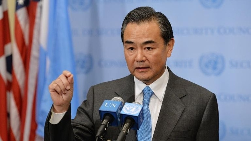 China's Foreign Minister Wang Yi speaks to the media after the UN Security Council voted to approve a resolution that will require Syria to give up its chemical weapons, on September 27, 2013 at the UN headquarters in New York