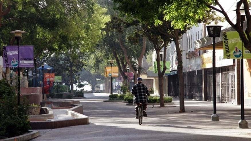 In this photo taken on Friday Sept. 20, 2013 in Fresno, Calif., a man rides his bike on the Fulton Mall, a six-block pedestrian mall once touted as a national model for pedestrian-friendly downtowns. While many U.S. cities are converting urban cores into walkable oases, Fresno leaders want to convert the struggling pedestrian mall back into a street. (AP Photo/Gosia Wozniacka)