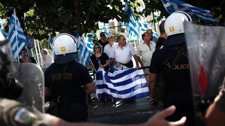 Supporters of the extreme far-right Golden Dawn party hold Greek flags as riot police tries to move them away during a protest in solidarity of the arrested lawmakers in front of the police headquarters in Athens on September 28, 2013.
