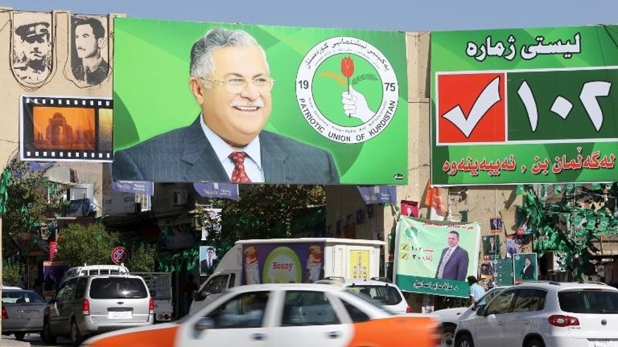 Vehicles drive past a giant poster featuring Iraqi President Jalal Talabani on September 18, 2013 in Iraq's northern city of Sulaimaniyah.