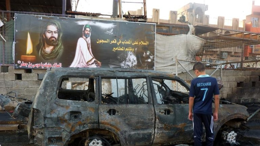 An Iraqi boy inspects a burnt out vehicle the day after a bomb attack in the Sadr City district of Baghdad on September 22, 2103