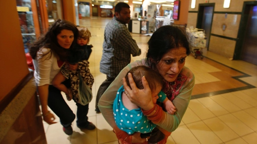 Sept. 21, 2013: Women carrying children run for safety as armed police hunt gunmen who went on a shooting spree in Westgate Mall in Nairobi, Kenya.