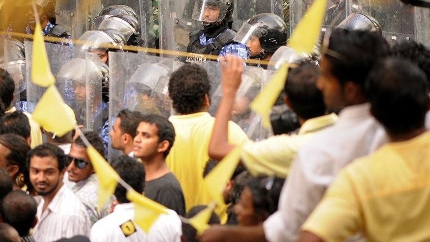 Activists from the Maldivian Democratic Party are watched by security personnel as they take part in a rally in Male on September 27, 2013