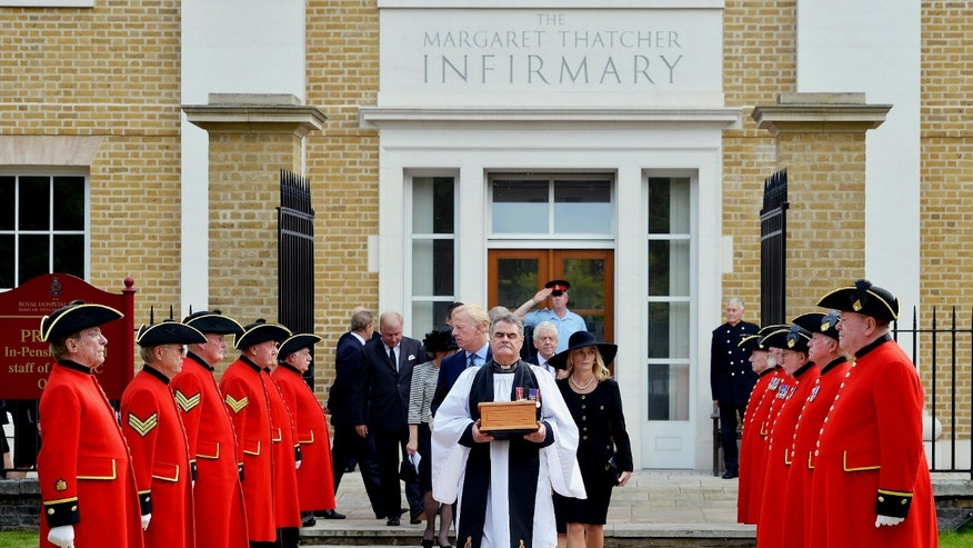 Sept. 28, 2013: Reverend Richard Whittington, foreground centre,  carries an oak casket containing the ashes of former British  Prime Minister Margaret Thatcher, followed by her daughter Carol, son Mark, centre left  and his wife Sarah, centre left,  after leaving the chapel,  at the Royal Hospital Chelsea.