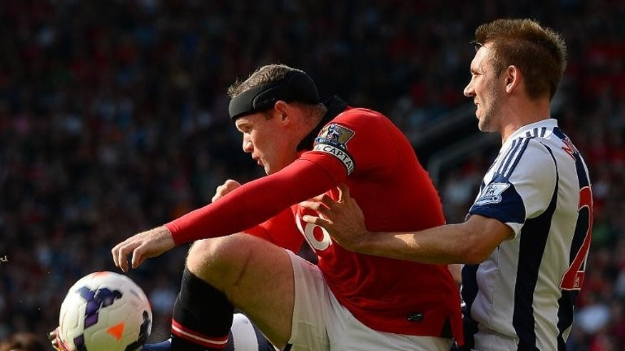 Manchester United's Wayne Rooney (L) gets to to the ball ahead of West Bromwich Albion's Gareth McAuley during their English Premier League match at Old Trafford in Manchester on September 28, 2013 which West Bromwich won 2-1.