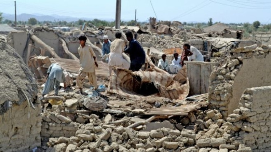 Sept. 25, 2013: Pakistani villagers look for belongings amid the rubble of their destroyed homes following an earthquake in the remote district of Awaran, Baluchistan province, Pakistan.