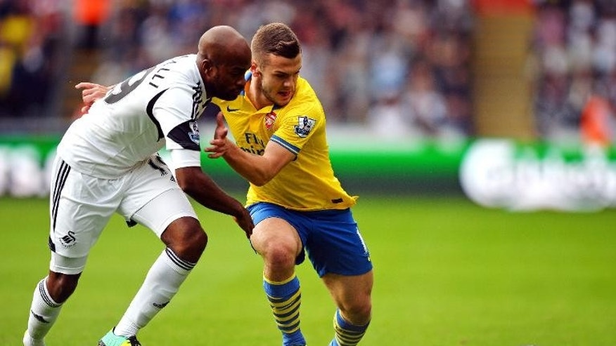 Swansea City's Dwight Tiendalli (L) tries to tackle Arsenal's Jack Wilshere during their English Premier League match at the Liberty Stadium in Swansea, south Wales on September 28, 2013 which Arsenal won 2-1