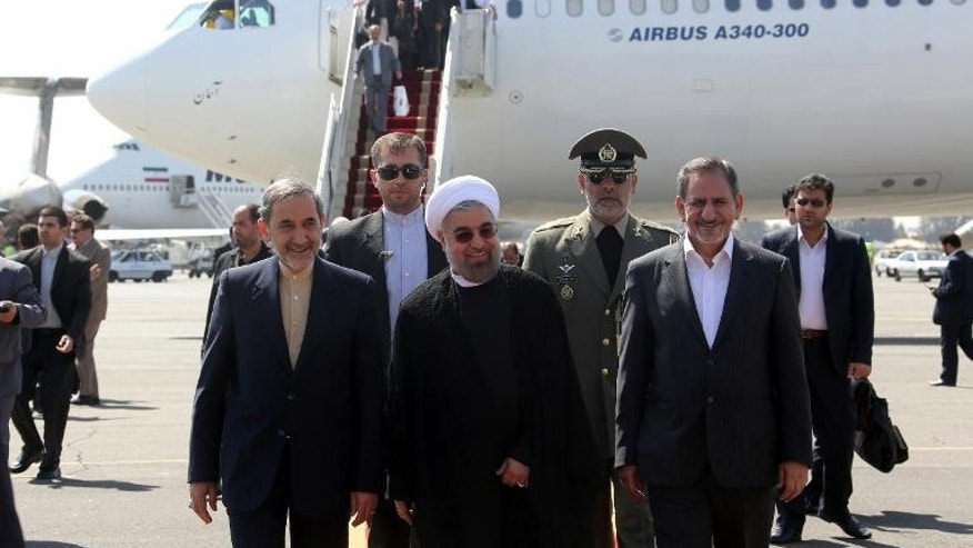 Iranian president Hassan Rouhani (C), Ali Akbar Velayati (L) advisor to the Islamic republic's supreme leader Ayatollah Ali Khamenei and Eshaq Jahangiri (R) the First Vice President arrive at Tehran's Mehrabad Airport, on September 28, 2013.
