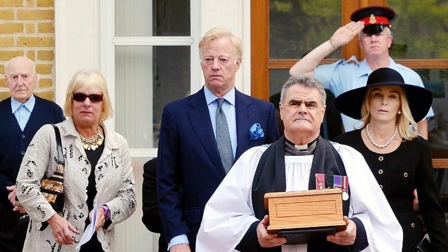Reverend Richard Whittington carries an oak casket with the ashes of late British former prime minister Margaret Thatcher, ahead of her daughter Carol (left), son Mark and his wife Sarah at the Royal Hospital Chelsea on September 28, 2013