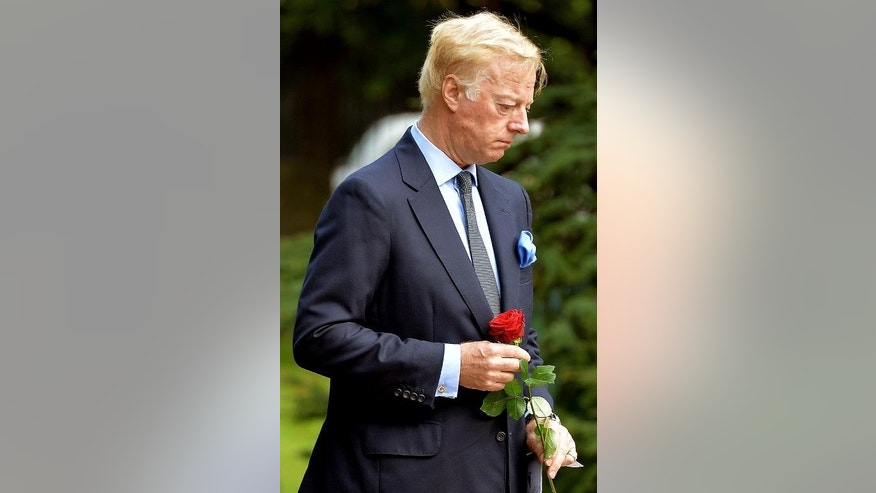 Mark Thatcher holds a red rose before placing it with the ashes of his mother, the late British former prime minister Margaret Thatcher, the Royal Hospital Chelsea, September 28, 2013