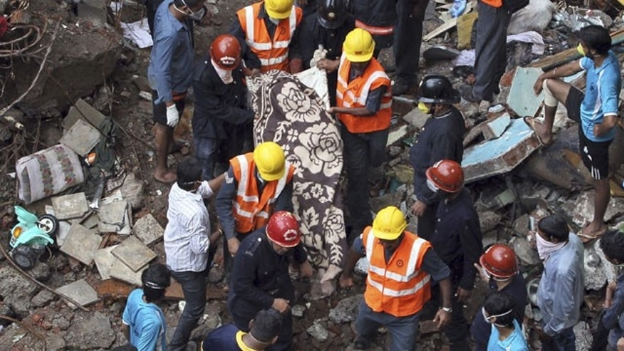 September 28, 2013: Rescue workers carry a dead body out of the debris of a building that collapsed in Mumbai, India.