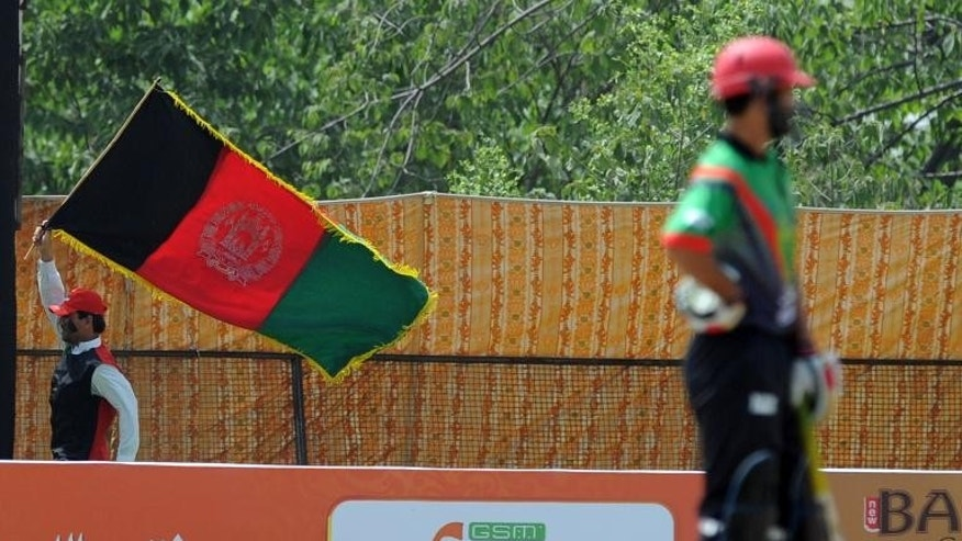An Afghan cricket fan waves his national flag as he cheers for his team at a local ground in Islamabad on May 25, 2011.