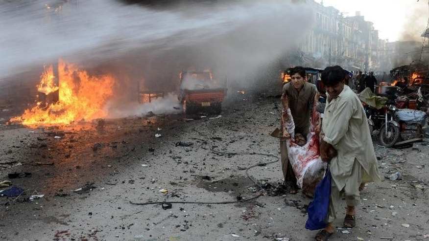 Pakistani men carry an injured blast victim at the site of a bomb explosion in the busy Kissa Khwani market in Peshawar on September 29, 2013 which killed at least 33 people