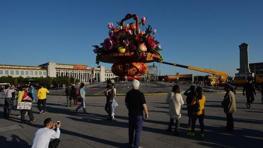 Tiananmen Square visitors watch as workmen install a giant vase containing fruit and flowers, on September 24, 2013