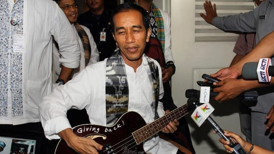 Jakarta Governor Joko Widodo on May 3, 2013 with a bass guitar given to him by Robert Trujillo of Metallica before turning it over to anti-corruption officials