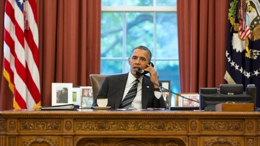 This official White House photograph released on September 27, 2013 shows President Barack Obama talking with President Hassan Rouhani of Iran during a phone call in the Oval Office.