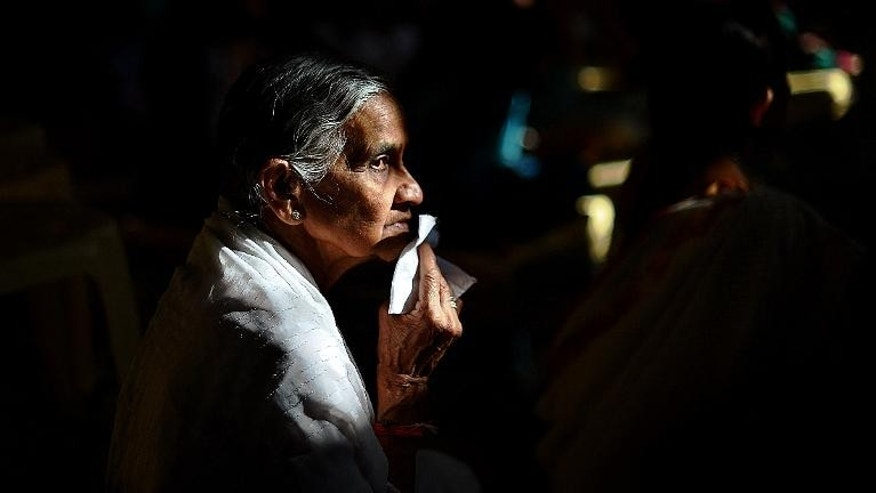 An elderly woman prays at Nairobi's Oshwal centre at the start of a Jain prayer vigil for victms of the Westgate mall massacre on September 28, 2013