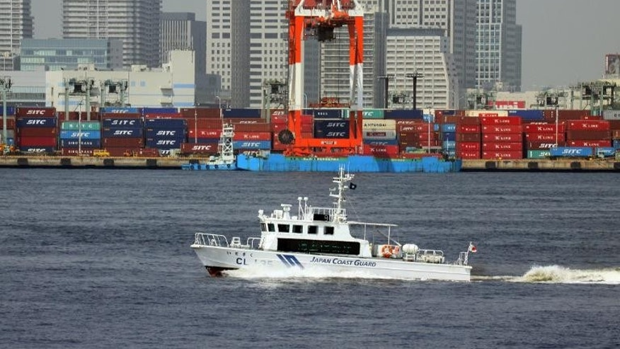A boat of Japan Coast Guard passes before the international cargo terminal in Tokyo on May 22, 2013