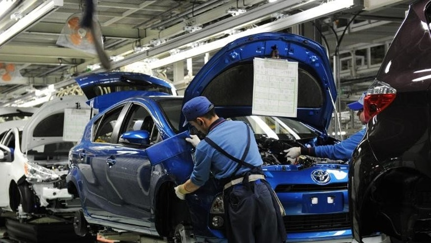 Workers assemble the front bumper of a Toyota compact hybrid vehicle at the Kanto Auto Works plant in Kanegasaki town, on March 9, 2012