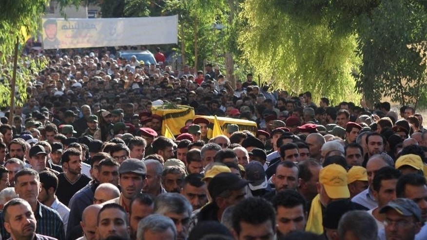 Lebanese Hezbollah militants carry the coffins of their two comrades killed the day before in a firefight with Sunni gunmen in the eastern Lebanese city of Baalbek, on September 29, 2013.