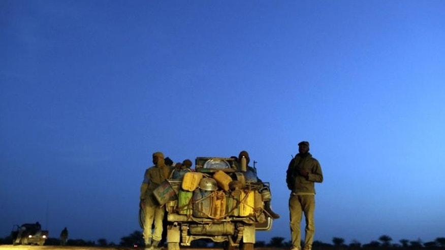Malian soldiers patrol on a road between Kidal and Gao on July 29, 2013 in northern Mali