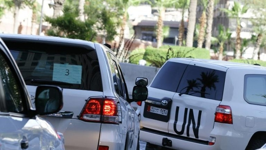 Vehicles carrying UN chemical weapons experts leave a Damascus hotel on September 26, 2013