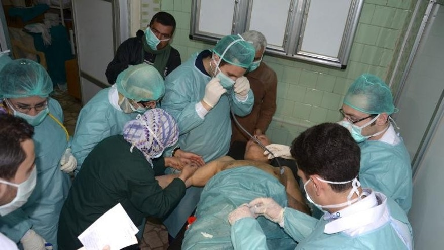 Medics attend to a man at a hospital in Khan al-Assal on March 19, 2013