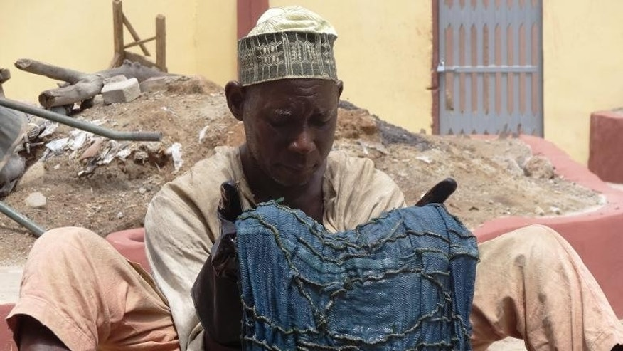 A dyer with cloth after dipping it in an indigo dye pit in Kano, Nigeria on September 8, 2013