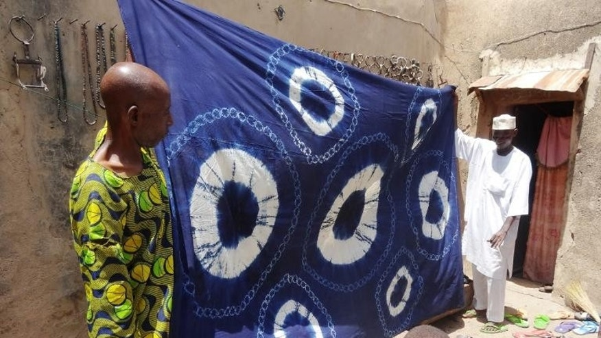 Two dyers hold out a finished indigo dyed cloth featuring the 'Bride and Groom' design in Kano, Nigeria on September 8, 2013