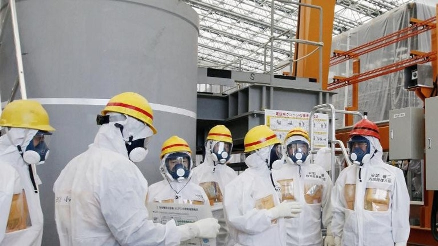 Japan PM Shinzo Abe (right) is briefed about the advanced liquid processing system (ALPS) on a visit to the stricken Fukushima nuclear power plant on September 19, 2013