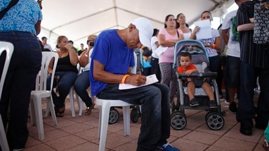 In this Sept. 25, 2013 photo, Jose Rodriguez fills out a contact form at a job fair in Catano, Puerto Rico. Puerto Rico's unemployment rate is 13.9 percent, the highest compared with any U.S. state.  (AP Photo/Ricardo Arduengo)