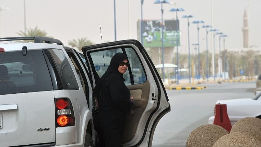 A Saudi woman gets out the backseat of a car on her way to a shopping mall in Riyadh on June 17, 2011