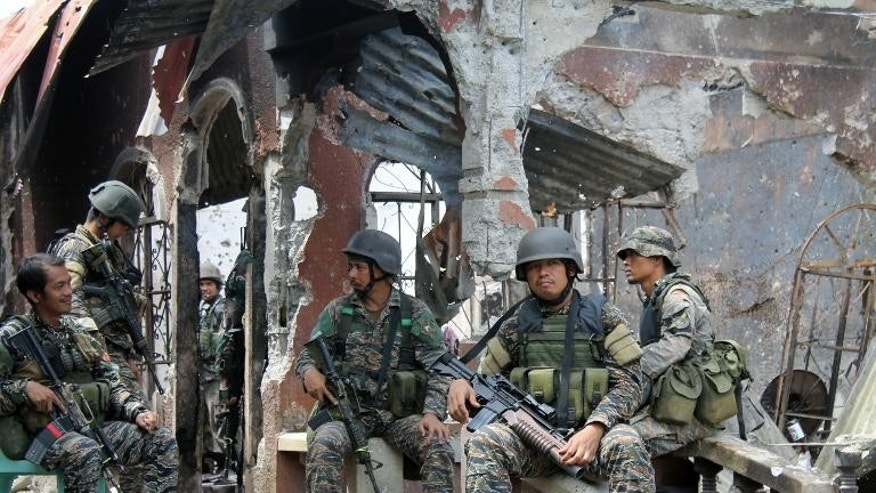 Philippine soldiers sit amongst burned houses destroyed during the stand-off with rebels in Zamboanga, on the southern island of Mindanao on September 28, 2013