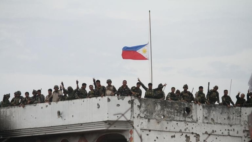 Philippine soldiers stand on the roof of a damaged house during a stand-off with rebels in Zamboanga, on the southern island of Mindanao on September 28, 2013