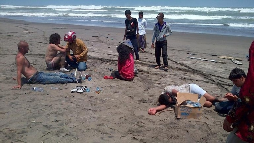 Residents help a group of asylum-seekers on the beach after being rescued by locals in the coastal village of Cianjur on September 27, 2013.