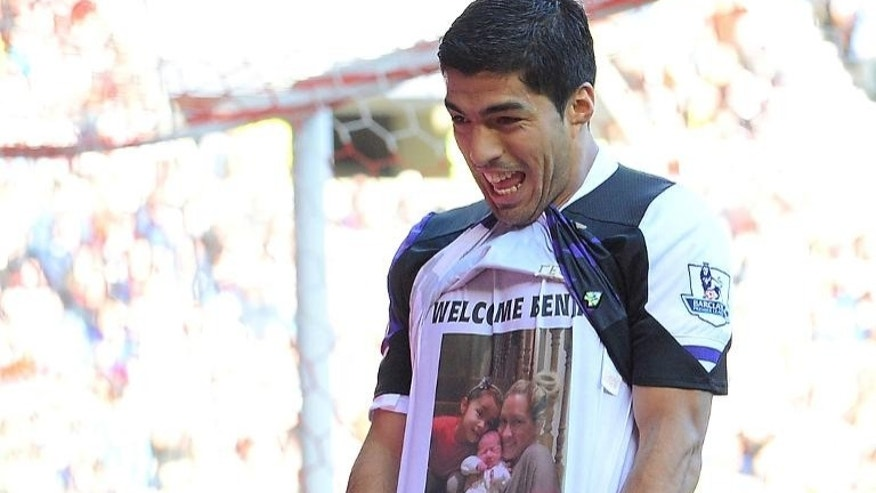 Liverpool's Uruguayan striker Luis Suarez celebrates by pulling up his jersey after scoring at the Stadium of Light in Sunderland, on September 29, 2013.