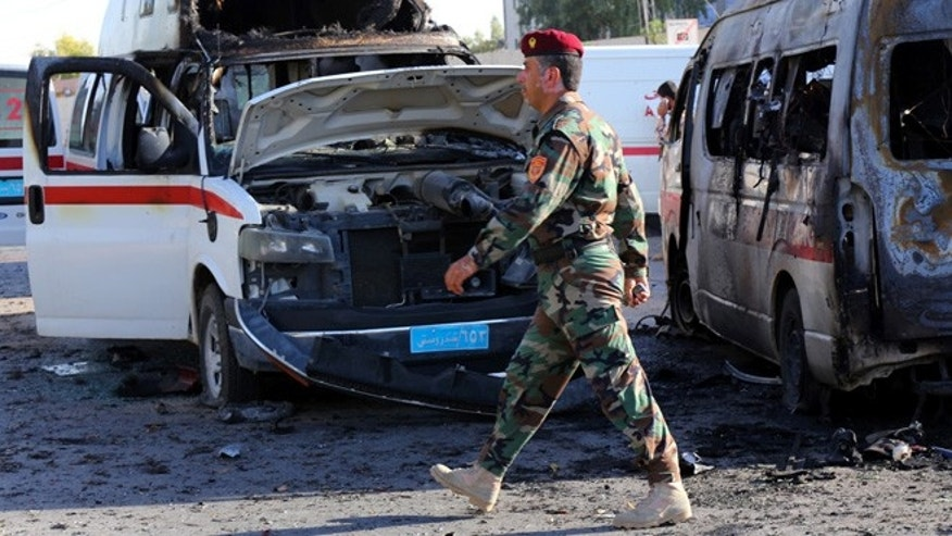 Sept. 29, 2013: A Kurdish policeman passes by destroyed ambulances at the site of a car bomb attack in front of the main security forces headquarters in Irbil, Iraq, 217 miles north of Baghdad. A twin suicide car bombing and ensuing firefight in the capital of Iraq's largely peaceful self-ruled northern Kurdish region killed and wounded dozens of security forces on Sunday, officials said.
