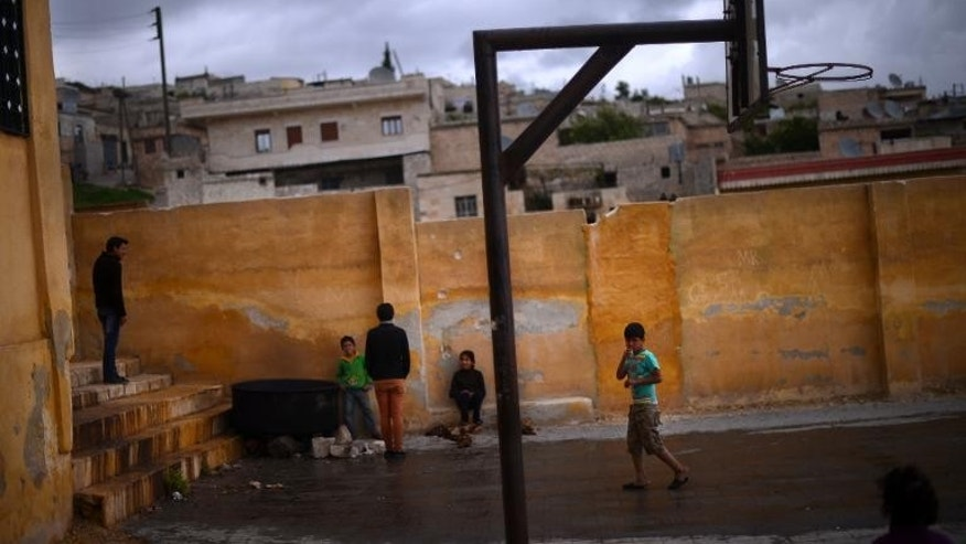 Boys play on a basketball court next to a school in Afrin, Syria, on April 9, 2013