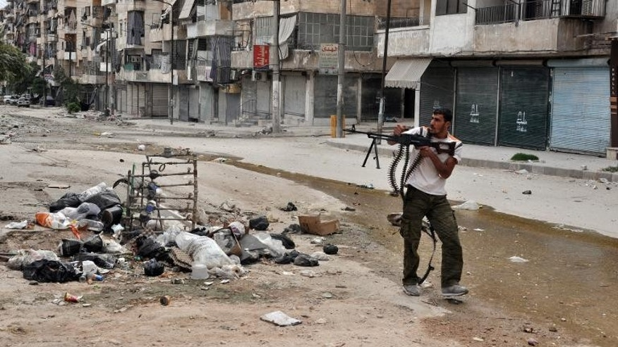 A rebel fighter fires at pro-government forces in the northern Syrian city of Aleppo on September 20, 2013