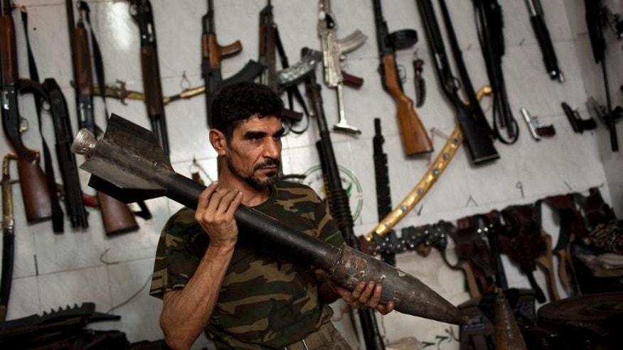 Abu Mohammad holds a home made rocket inside his gun shop in Aleppo, Syria on September 21, 2013