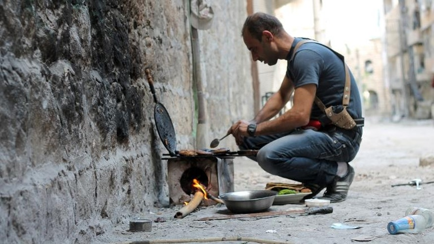 A rebel fighter cooks food on a stove in Syria's Aleppo on September 25, 2013