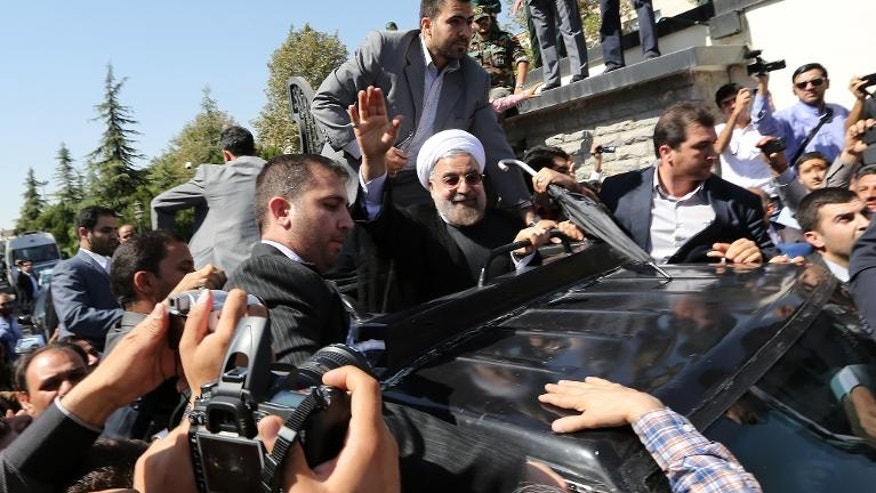 Iranian President Hassan Rouhani waves as his motorcade leaves Tehran's Mehrabad Airport on September 28, 2013.
