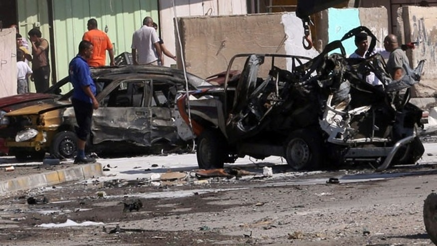September 30, 2013: Citizens inspect the site of a car bomb attack in Baghdad. (AP Photo)