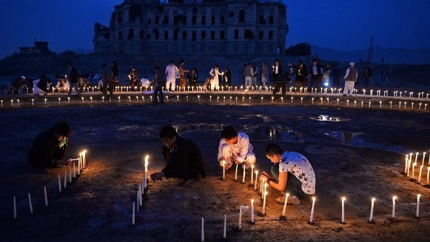 Afghan youth light candles in front of the destroyed palace of Darul Aman to mark the killing of 5000 civilians by the communist regime during the Russian occupation, in Kabul on September 29, 2013