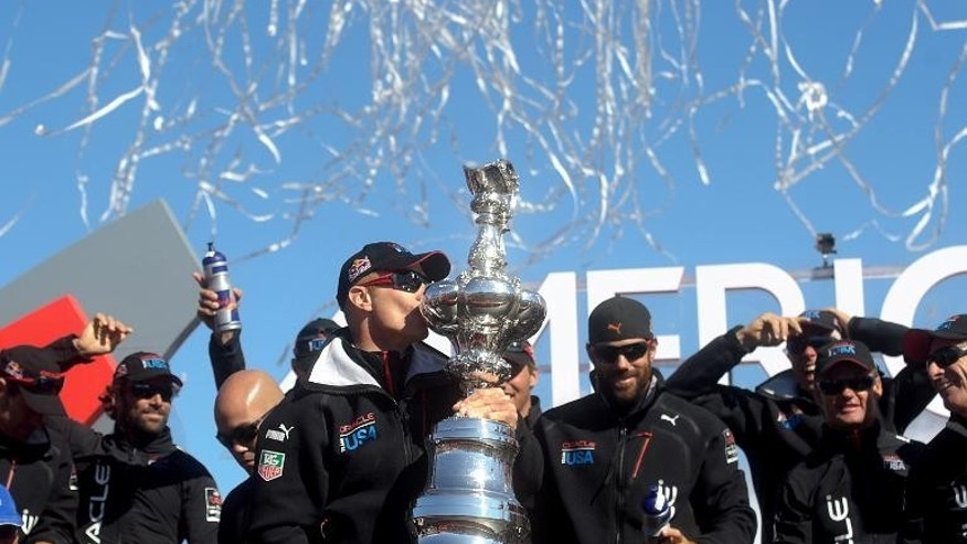 Oracle Team USA skipper Jimmy Spithill kisses the America's Cup trophy while celebrating his team's victory over Emirates Team New Zealand in the 34th America's Cup on September 25, 2013, in San Francisco